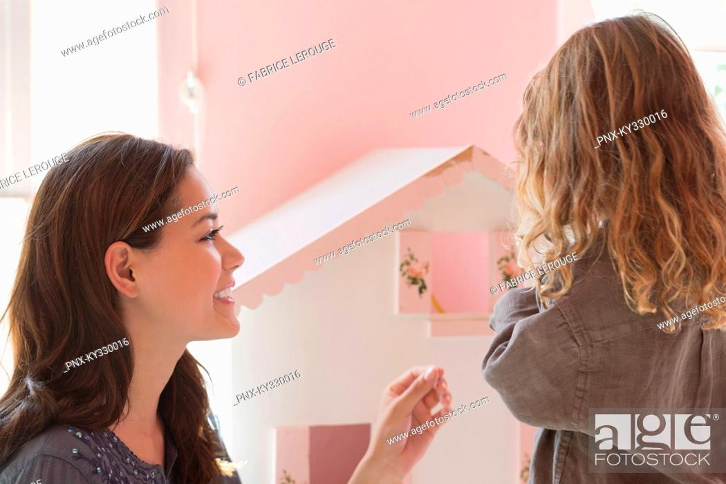 Stock Photo: Happy mother playing with daughter at home.