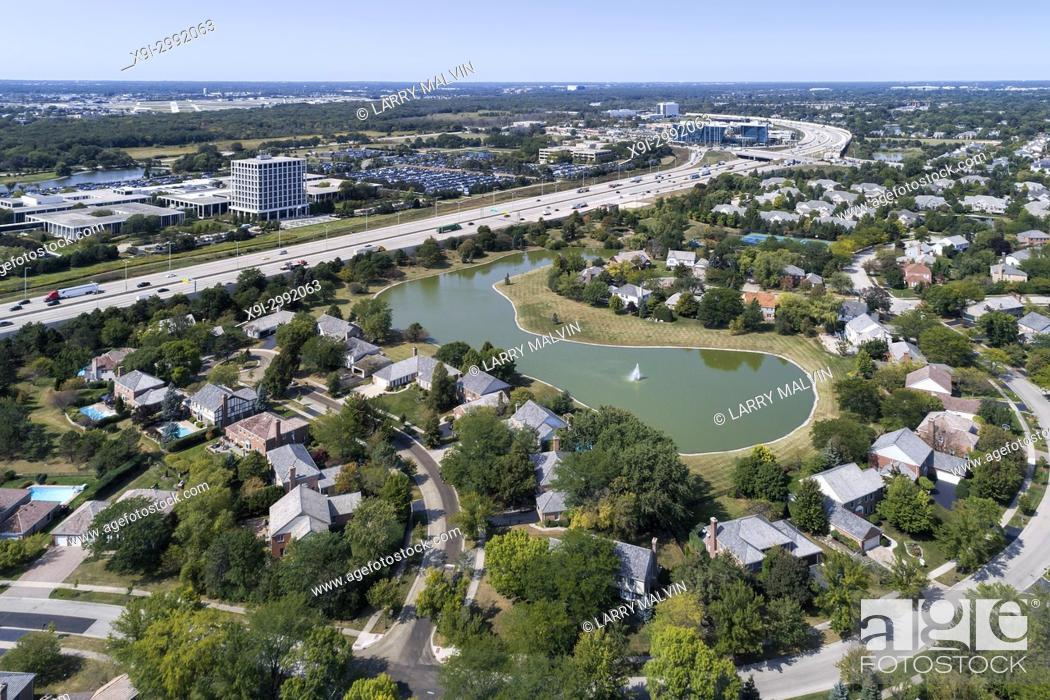 Stock Photo: Aerial view of a neighborhood with pond beside a major highway in the suburb of Glenview, IL. USA.