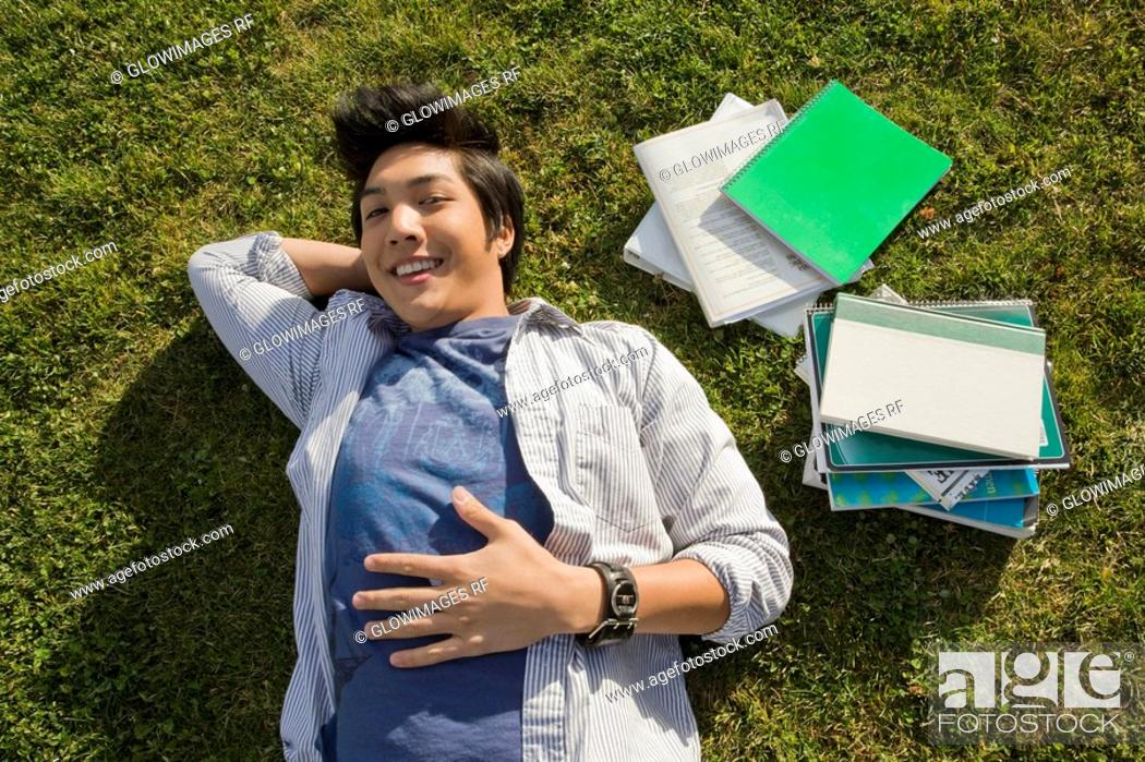 Stock Photo: High angle view of a young man lying in a lawn.