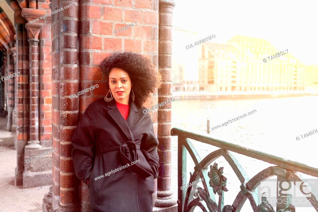 Stock Photo: Mid adult woman in stylish coat on Oberbaum Bridge, portrait, Berlin, Germany.