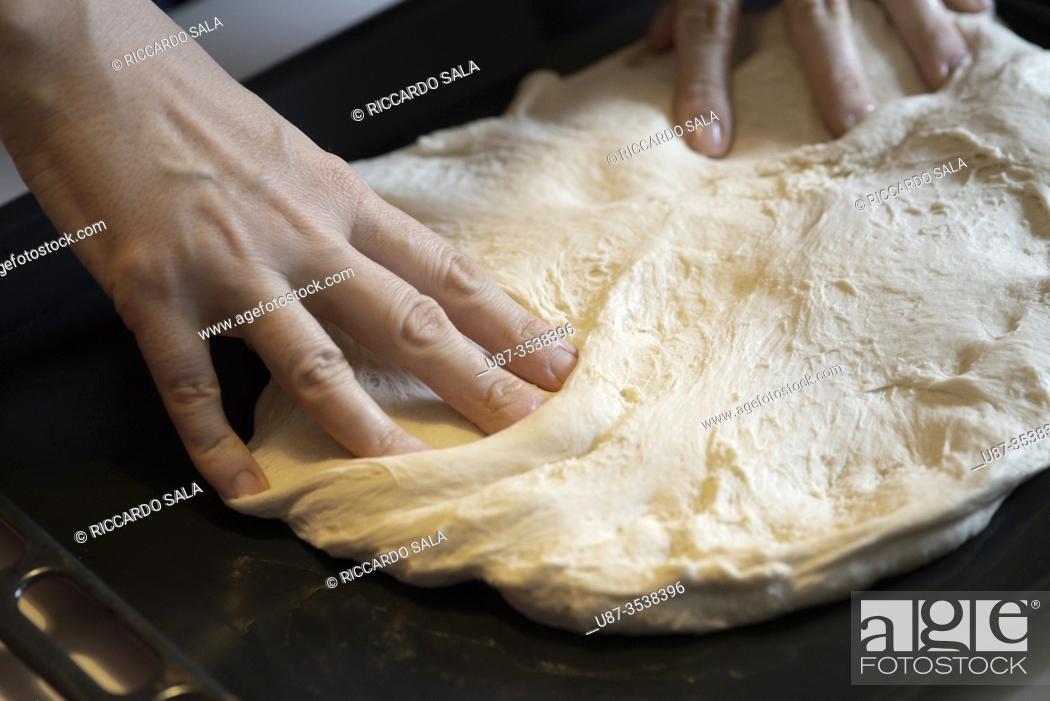 Photo de stock: Pressing Pizza Dough Into Oven Tray. . .