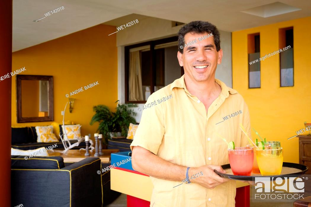 Stock Photo: Smiling hispanic man, 50 years old, is serving cocktails on a tray.