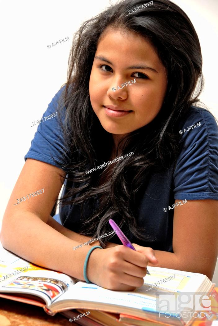 Stock Photo: 16 years old teen age girl doing her home work.