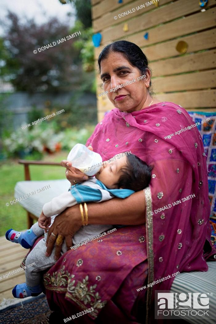 Photo de stock: Indian grandmother feeding bottle to grandson.