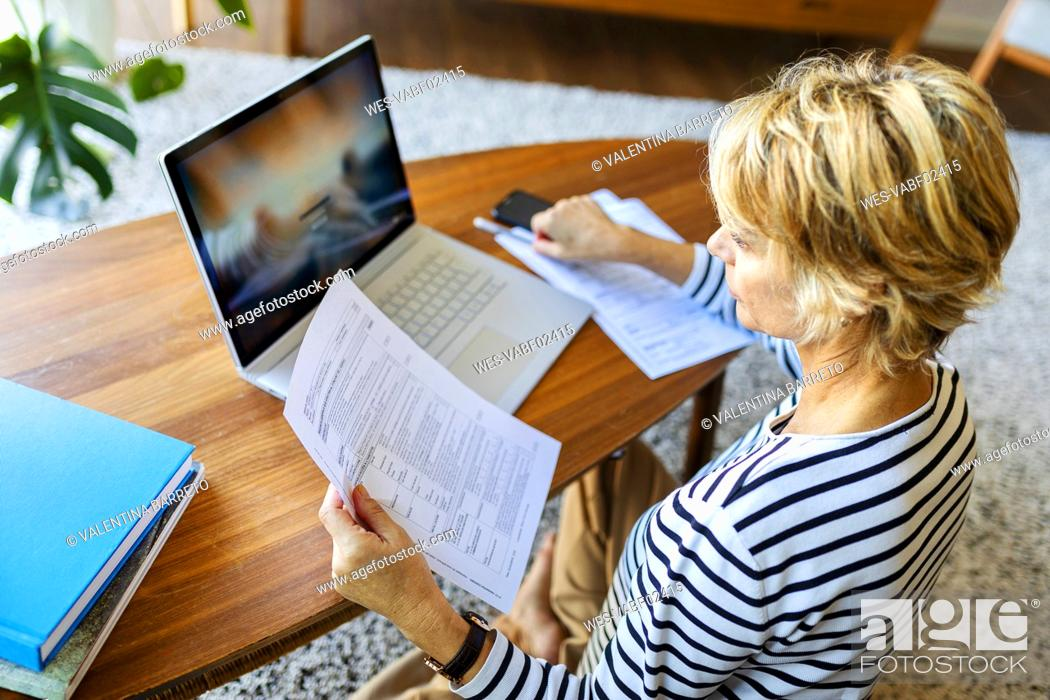 Stock Photo: Mature woman with documents using laptop at home.