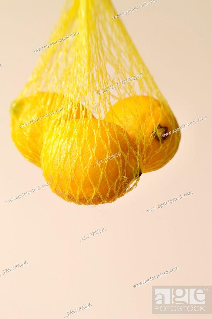 Stock Photo: Lemons hanging in net, white background.