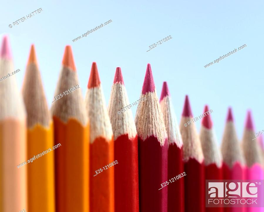 Stock Photo: A row of coloured pencils photographed where the red pencil in the middle is in selective focus.