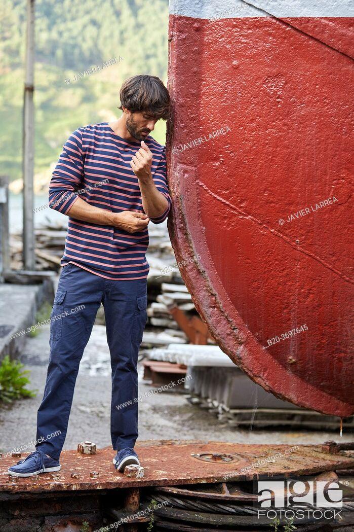 Stock Photo: Young man walking in shipyard, ship in the port of Pasaia, Gipuzkoa, Basque Country, Spain, Europe.