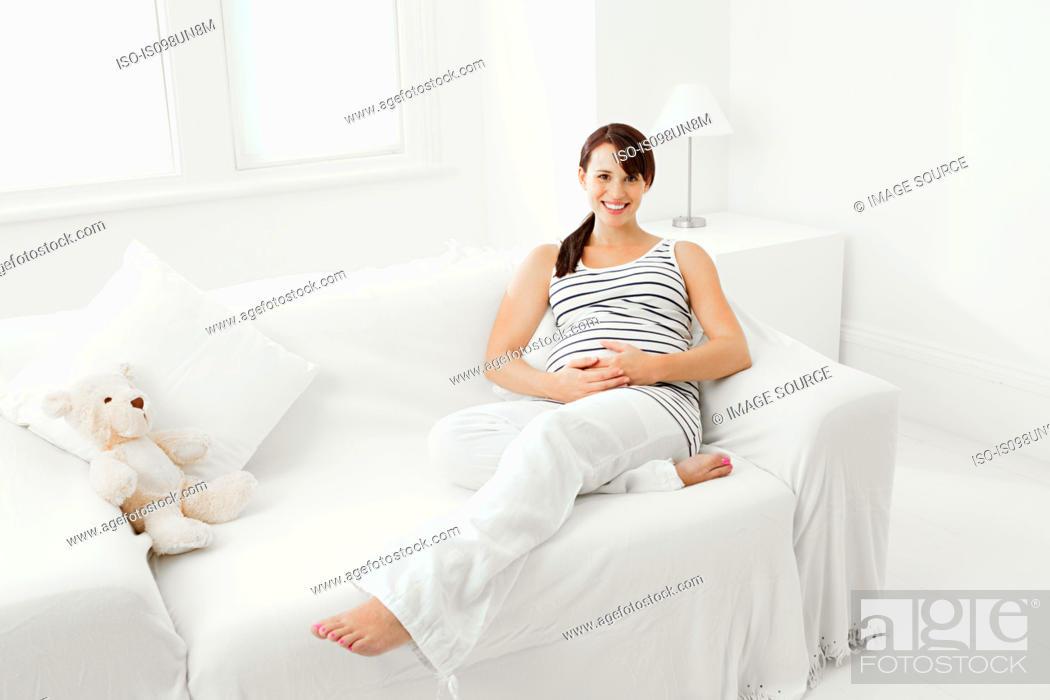 Stock Photo: Pregnant woman sitting on sofa.