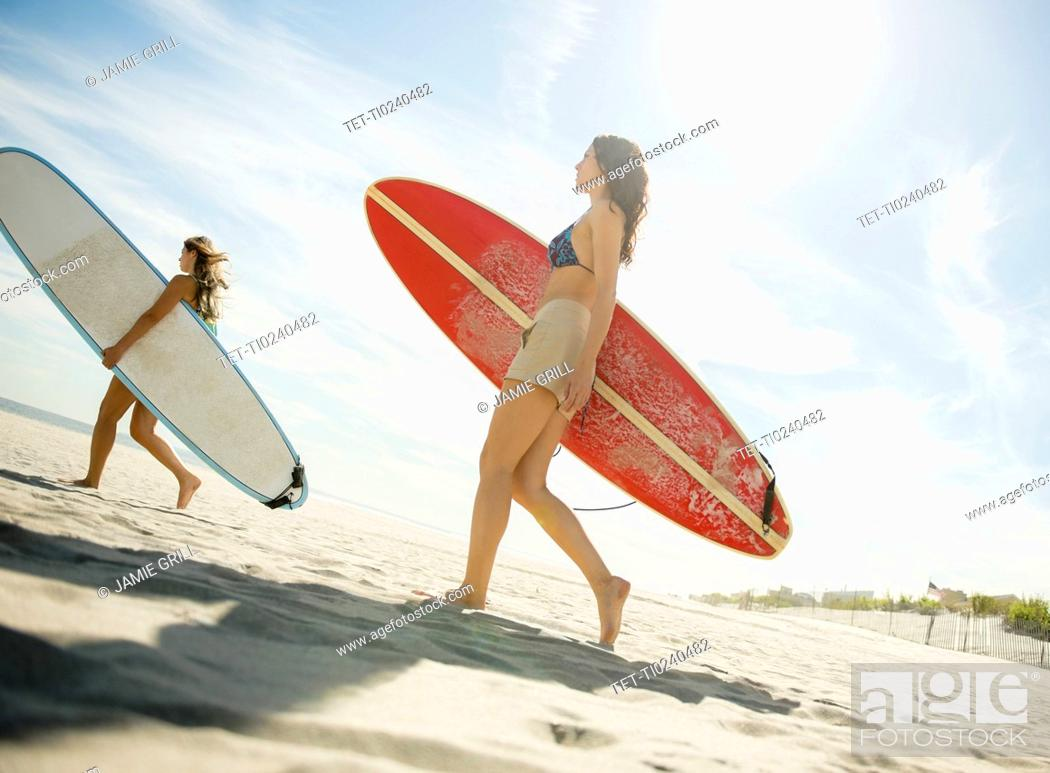 Stock Photo: Two women carrying surfboards on beach.
