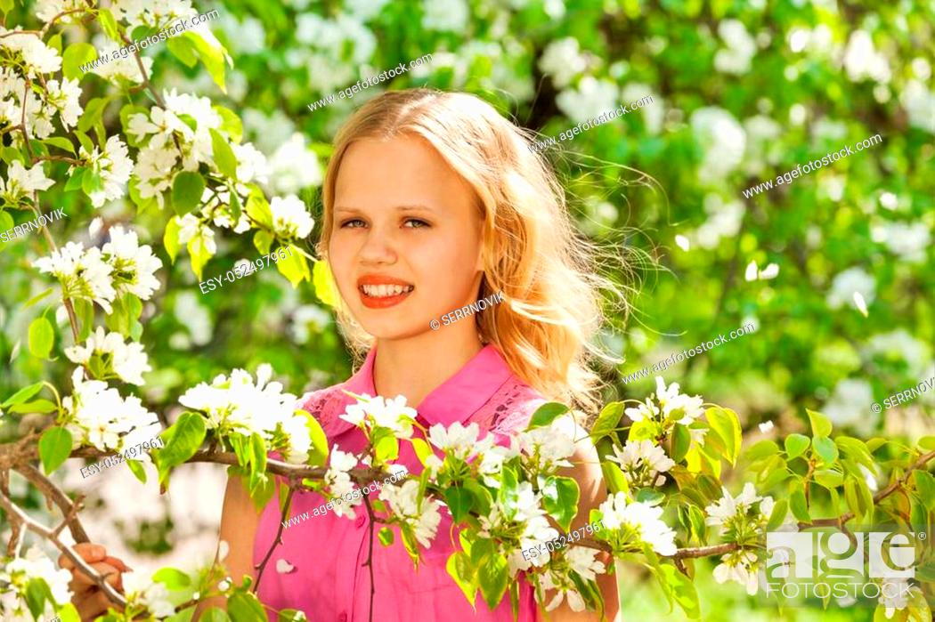 Stock Photo: Cute teenager blond girl with white flowers on pear tree during sunny summer day in green park.