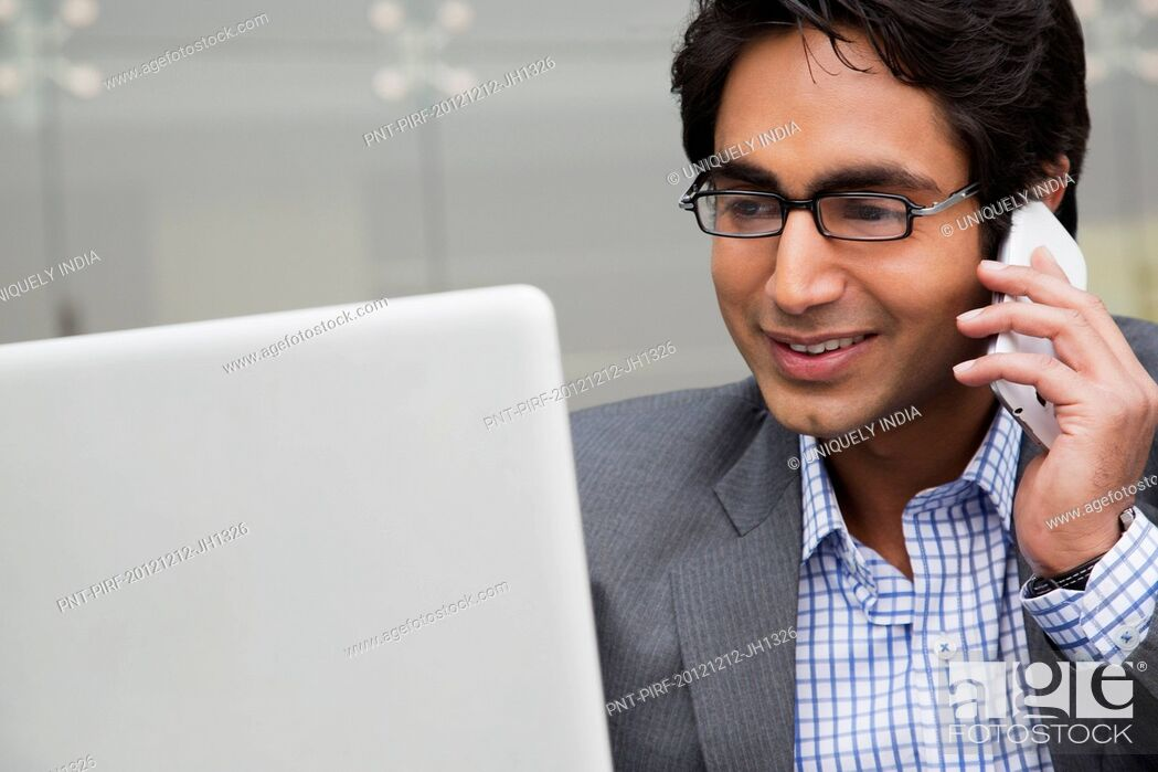 Stock Photo: Businessman using a laptop while talking on a mobile phone.