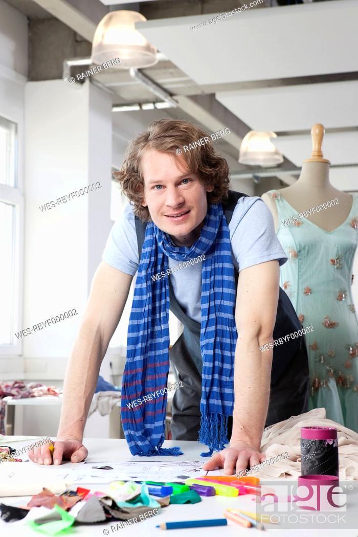 Stock Photo: Germany, Bavaria, Munich, Fashion designer working, portrait.