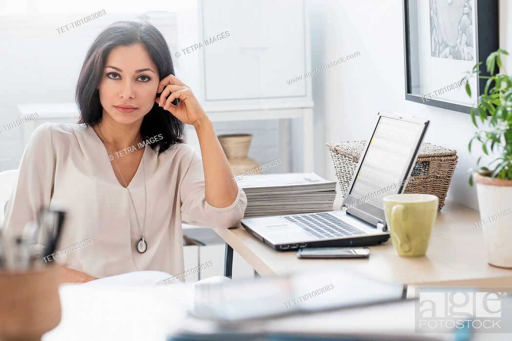 Stock Photo: Woman sitting at desk with laptop.