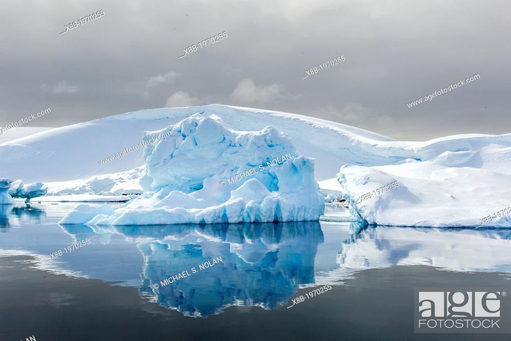 Imagen: Snow-capped mountains surround the Enterprise Islands, Antarctica, Southern Ocean.