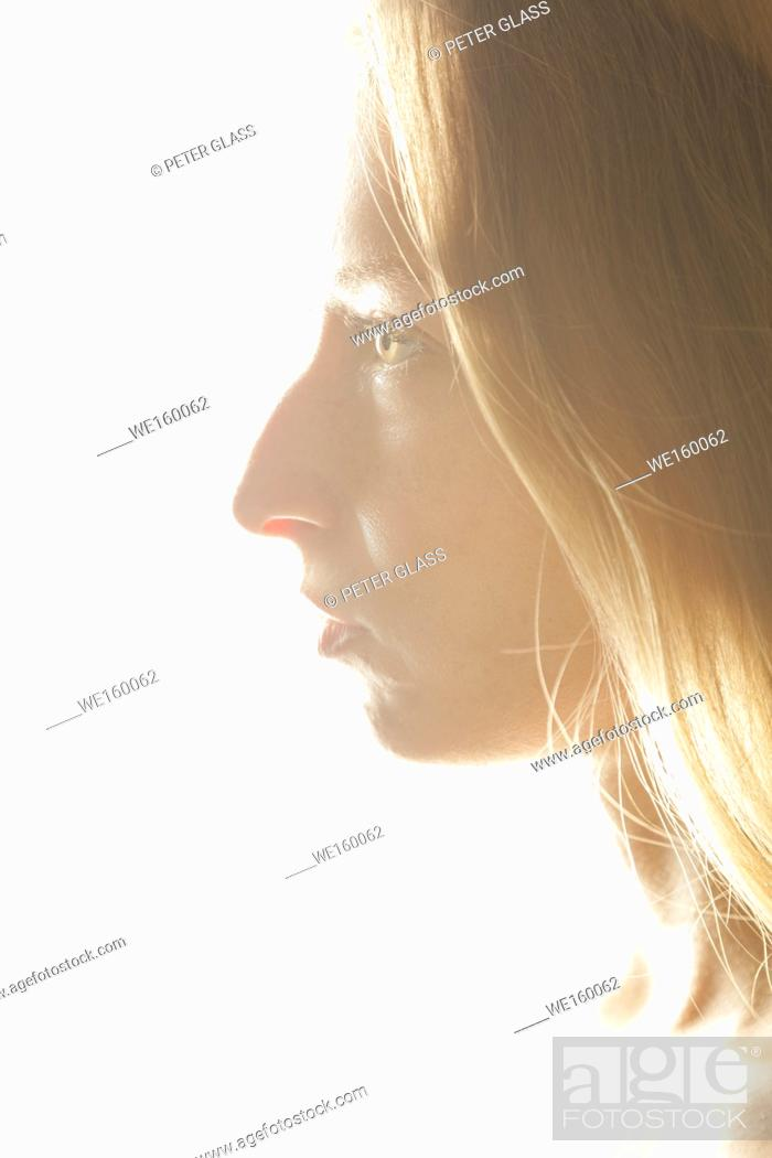 Stock Photo: Profile of a young woman's face in front of a bright white background.