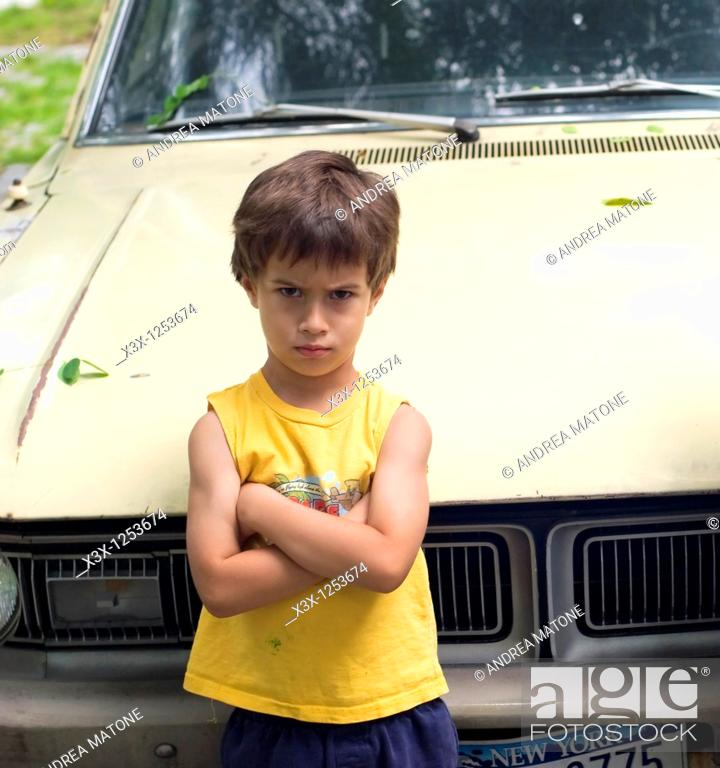Stock Photo: An upset child leaning on a car.