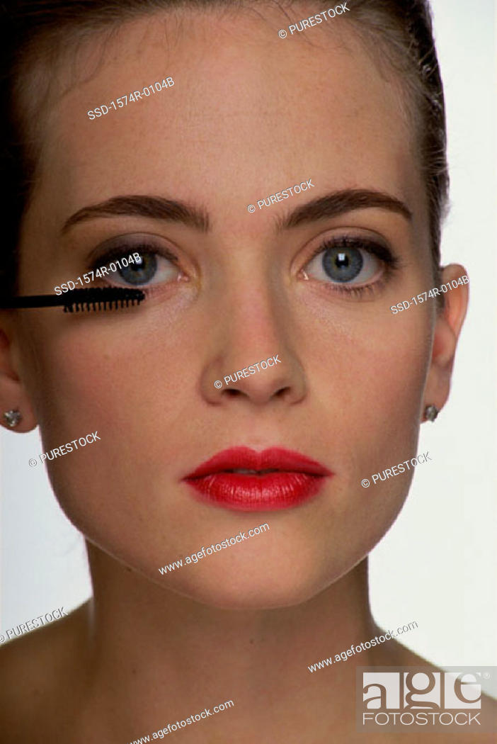 Stock Photo: Close-up of a young woman applying mascara with a brush.