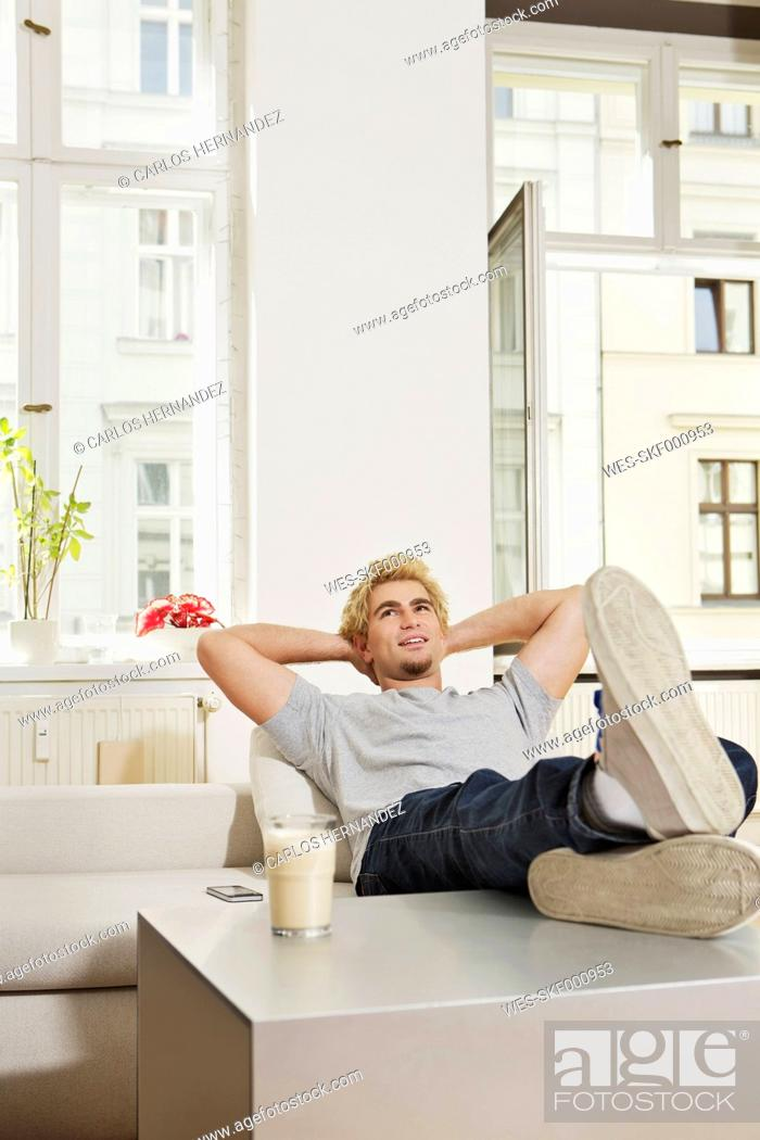 Stock Photo: Germany, Berlin, Young man sitting in living room, smiling.