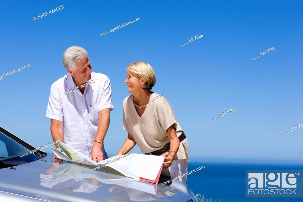 Stock Photo: Senior couple standing beside bonnet of parked car on clifftop overlooking Atlantic Ocean, consulting map, smiling.