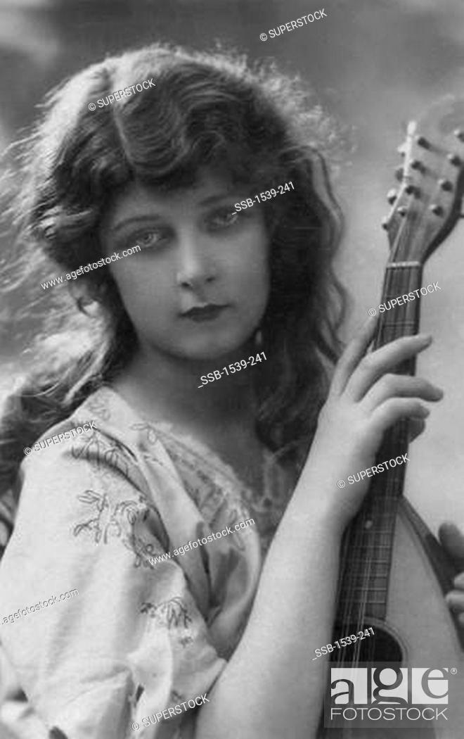 Stock Photo: French postcard of beautiful young woman with Neapolitan style mandolin, c. 1912.