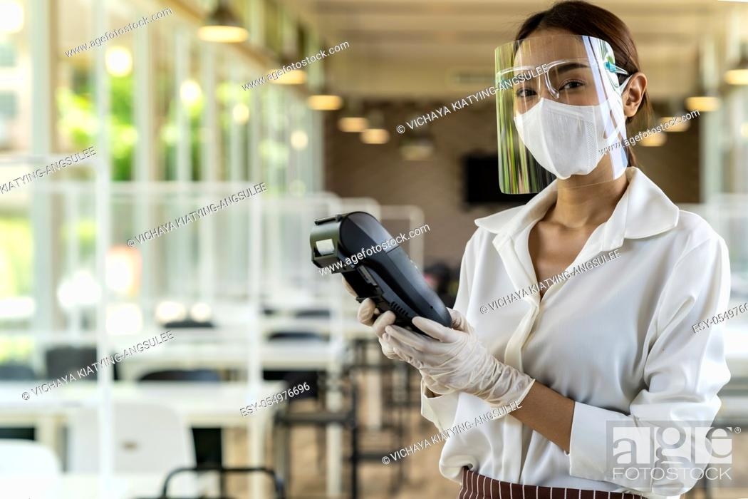 Stock Photo: Portrait attractive asian waitress wear face mask and face shield hold credit card reader for contactless payment with indoor restaurant background.