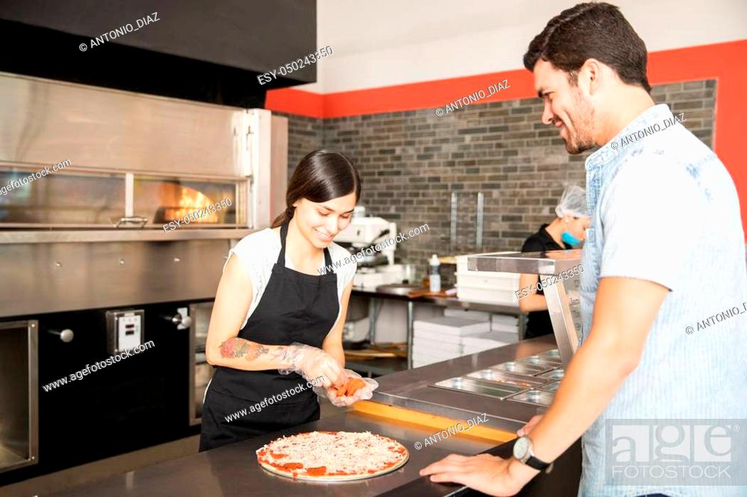 Stock Photo: Beautiful chef preparing pepperoni pizza for customer standing at kitchen counter in pizza shop.