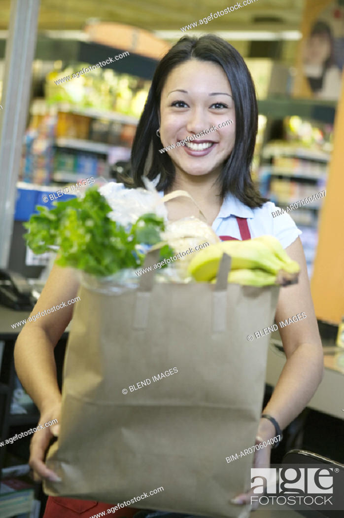 Stock Photo: Woman holding bag of groceries.