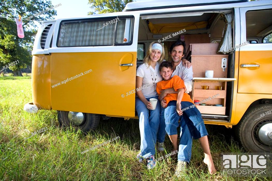Stock Photo: Family of three in camper van, boy 10-12 on father's lap, smiling, portrait.