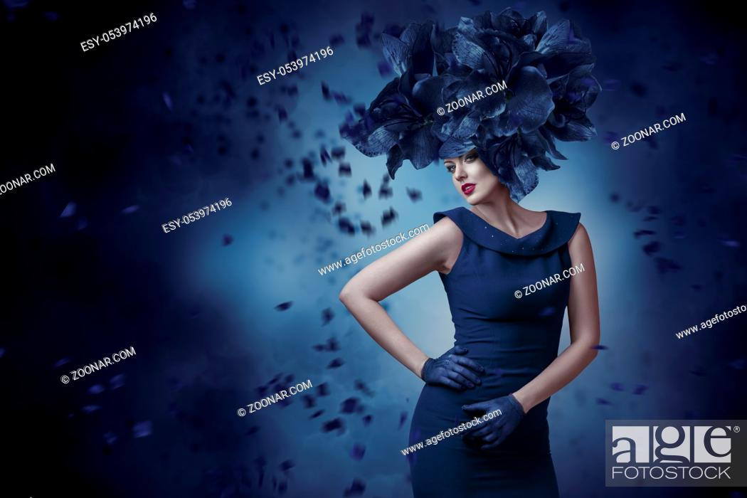 Stock Photo: Fashion portrait of young woman posing in fantasy hat.