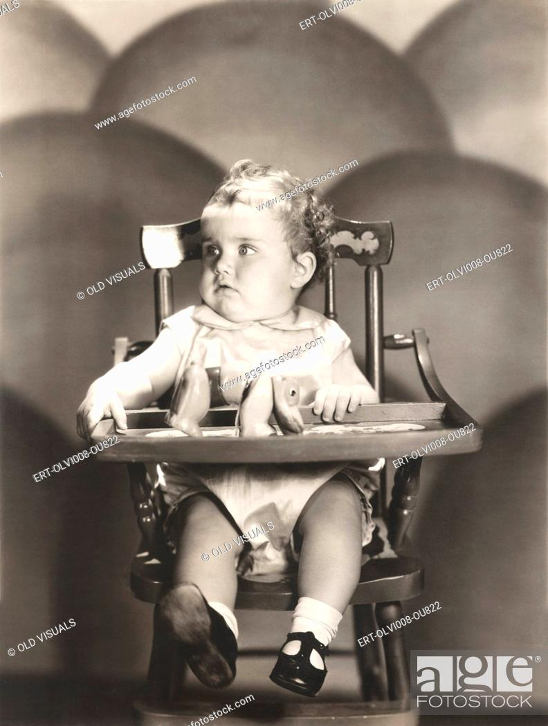 Stock Photo: Cute baby sitting on high chair.