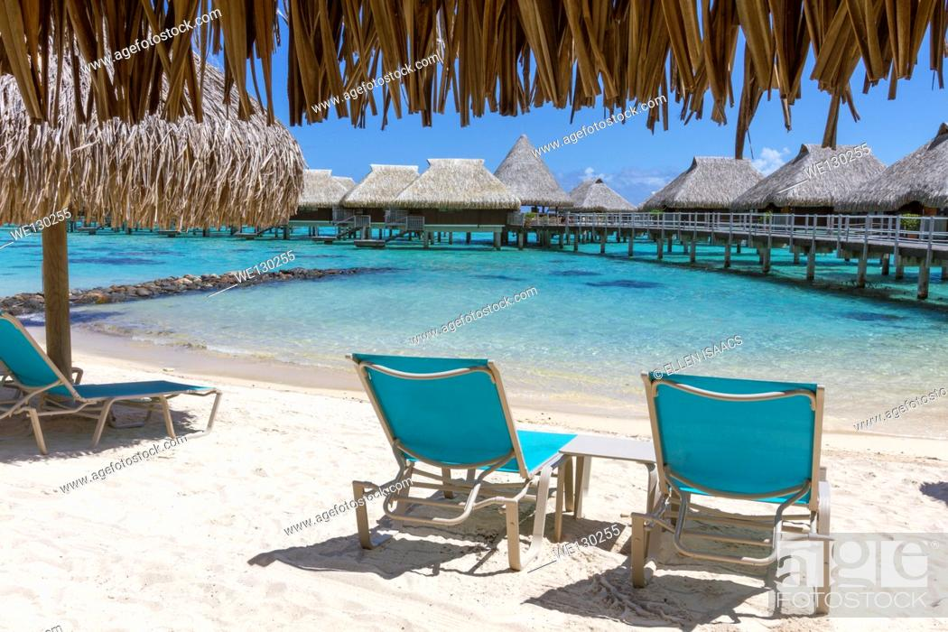 Stock Photo: Lounge chairs on beach by thatched roof hut overlooking overwater bungalows in French Polynesia.