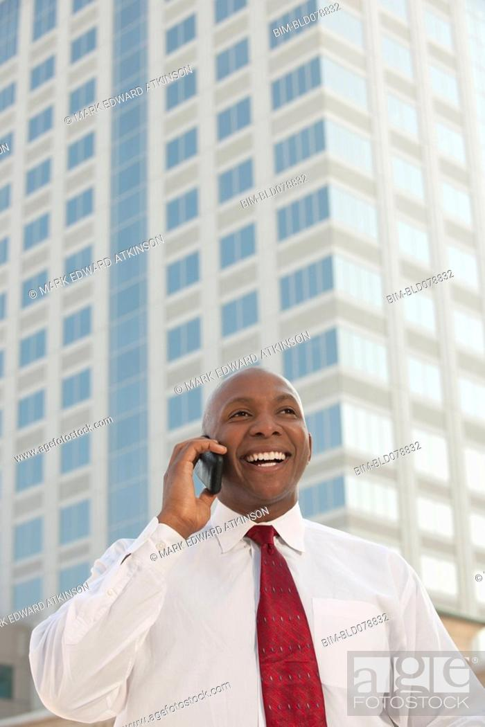Stock Photo: Black businessman talking on cell phone outdoors.