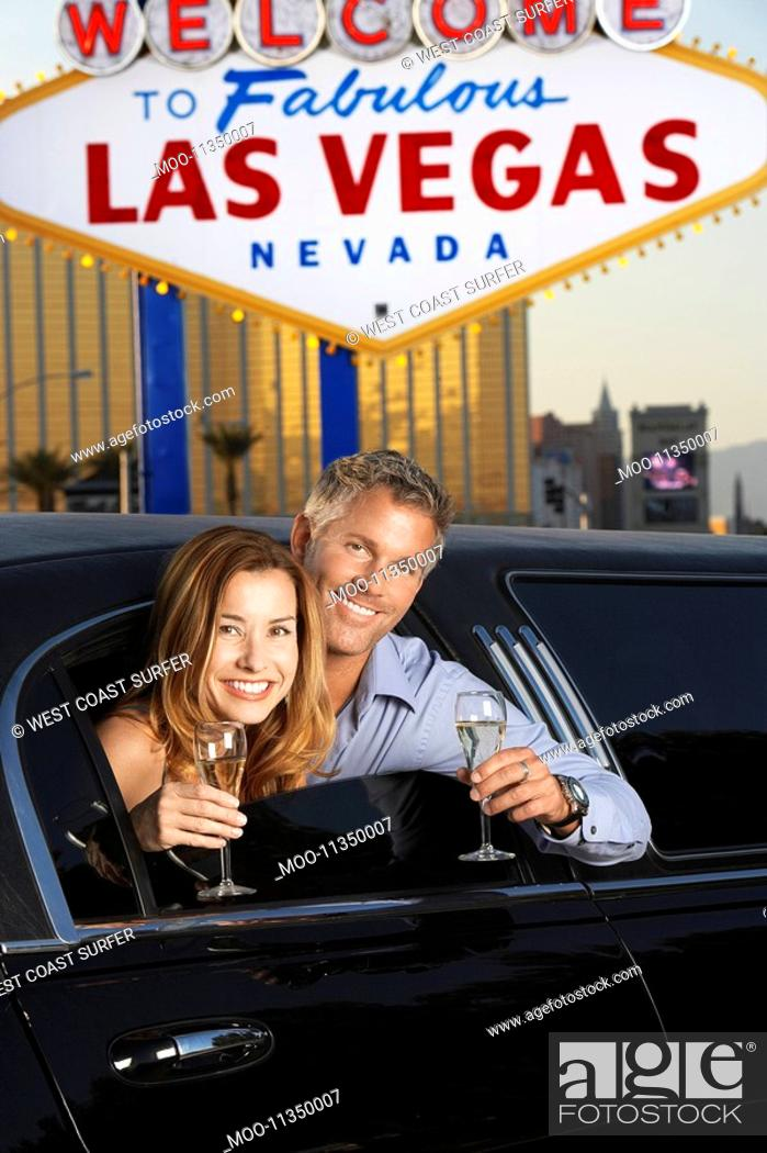 Stock Photo: Couple sitting in limousine with drinking glasses in front of Welcome to Las Vegas sign.