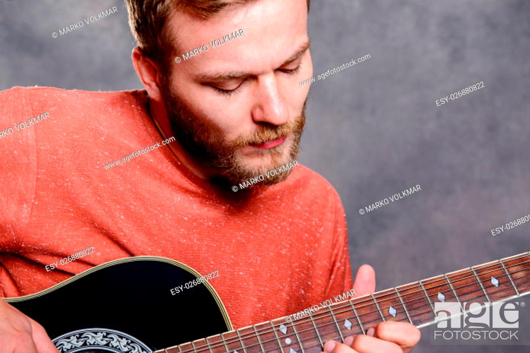 Imagen: young bearded man in red shirt playing acoustic guitar.