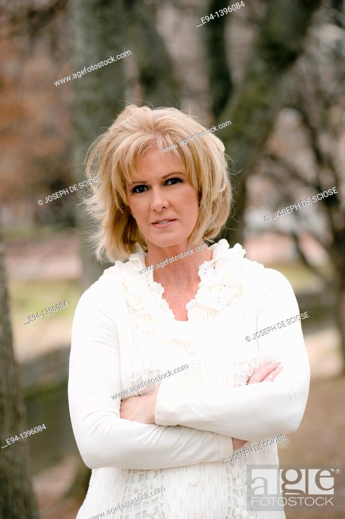 Stock Photo: Portrait of a 50 year old blond woman in an outdoor setting smiling at the camera.