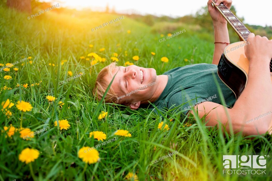 Stock Photo: Young man lying in grass playing guitar.