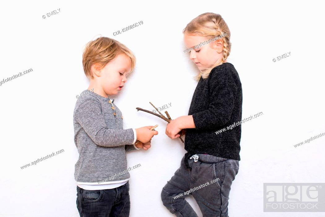 Stock Photo: Young girl and boy leaning against white background, girl holding twigs.