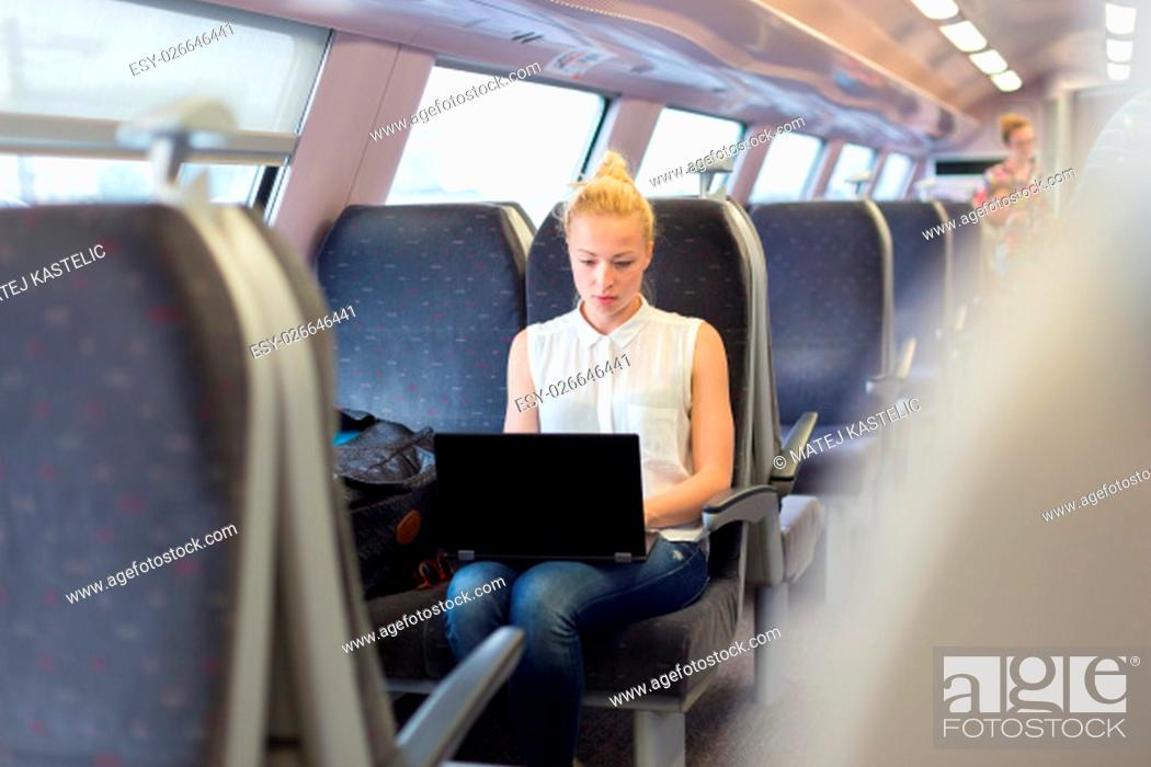 Stock Photo: Businesswoman sitting and traveling by train working on laptop.