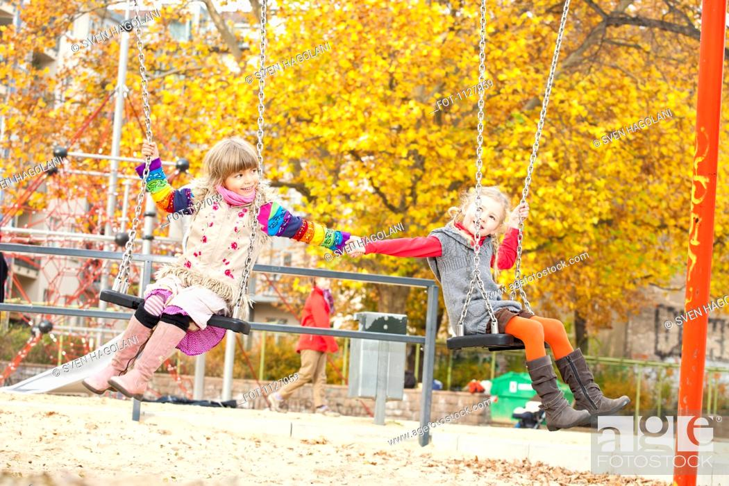 Stock Photo: Two girls on swings holding hands.