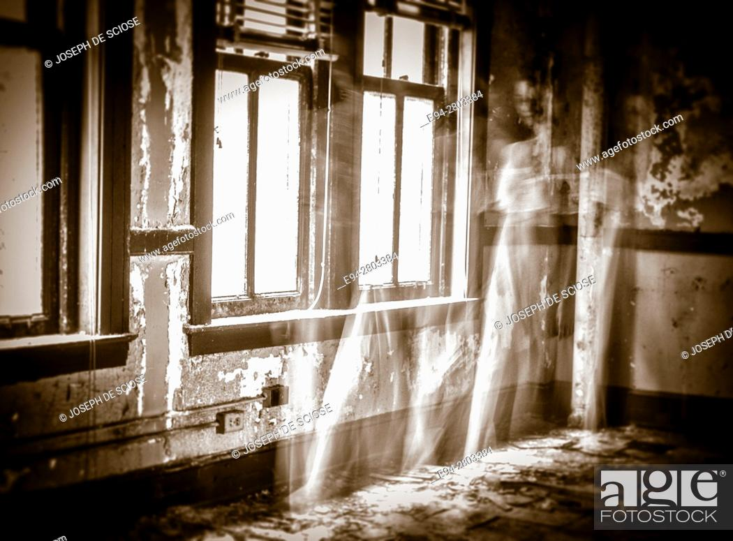 Photo de stock: A ghostly figure of a woman in a white dress moving a room in an abandoned building.