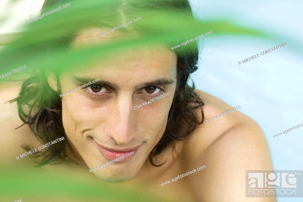 Stock Photo: Man smiling at camera through foliage, portrait.