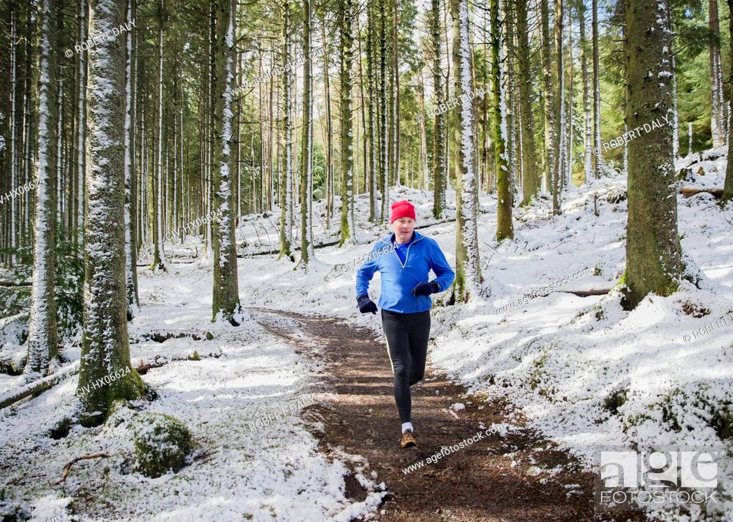 Stock Photo: Senior man jogging in snowy woods.