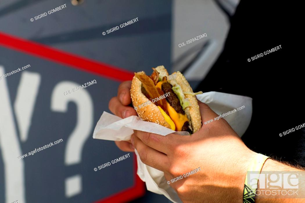 Stock Photo: Male customer's hand eating hamburger from fast food van.