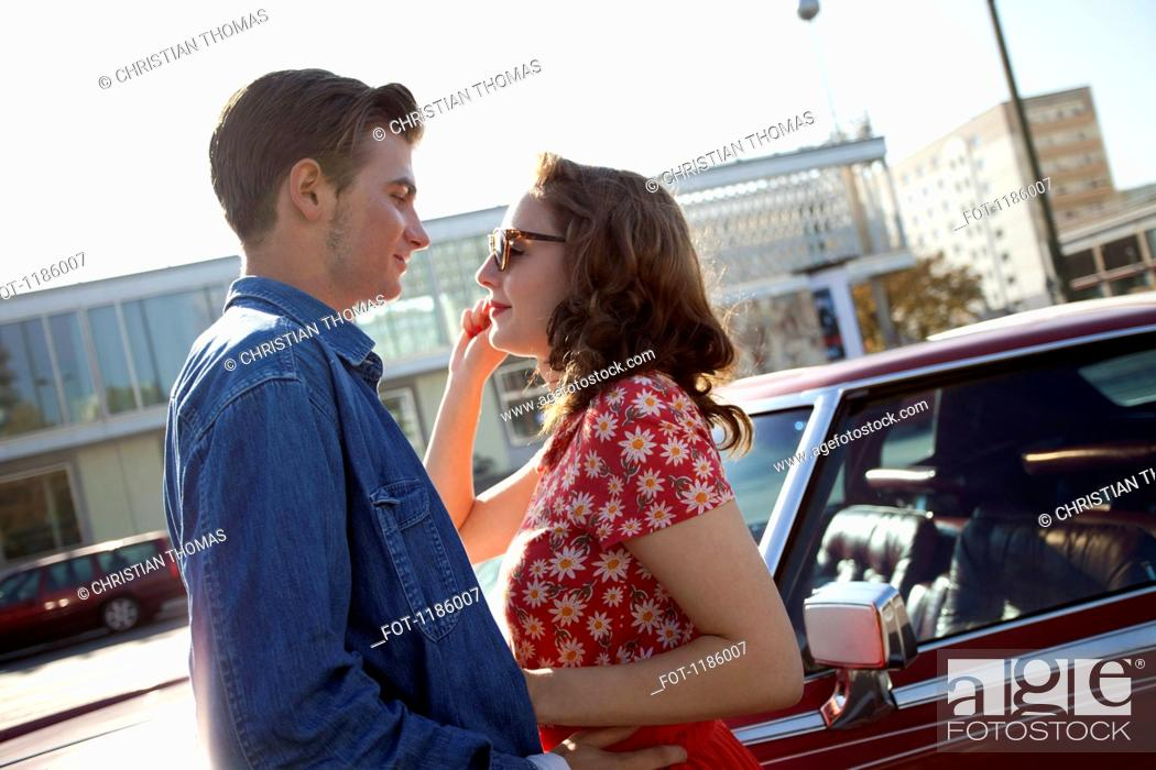 Stock Photo: A rockabilly couple standing face to face next to a vintage car.