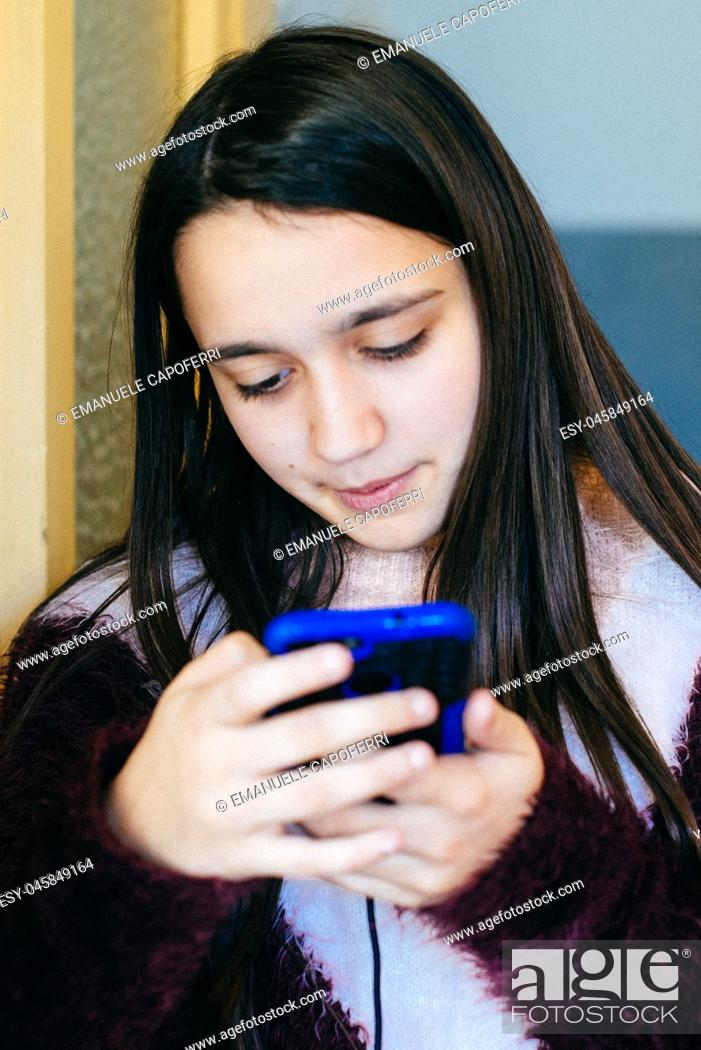 Stock Photo: girl looks at the smartphone-portrait of absorbed little girl in the phone screen.