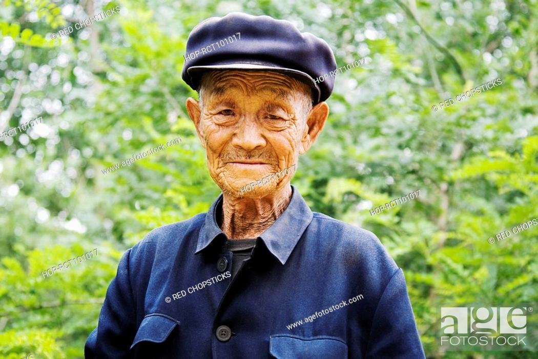 Stock Photo: Portrait of a senior man wearing a flat cap, Zhigou, Shandong Province, China.