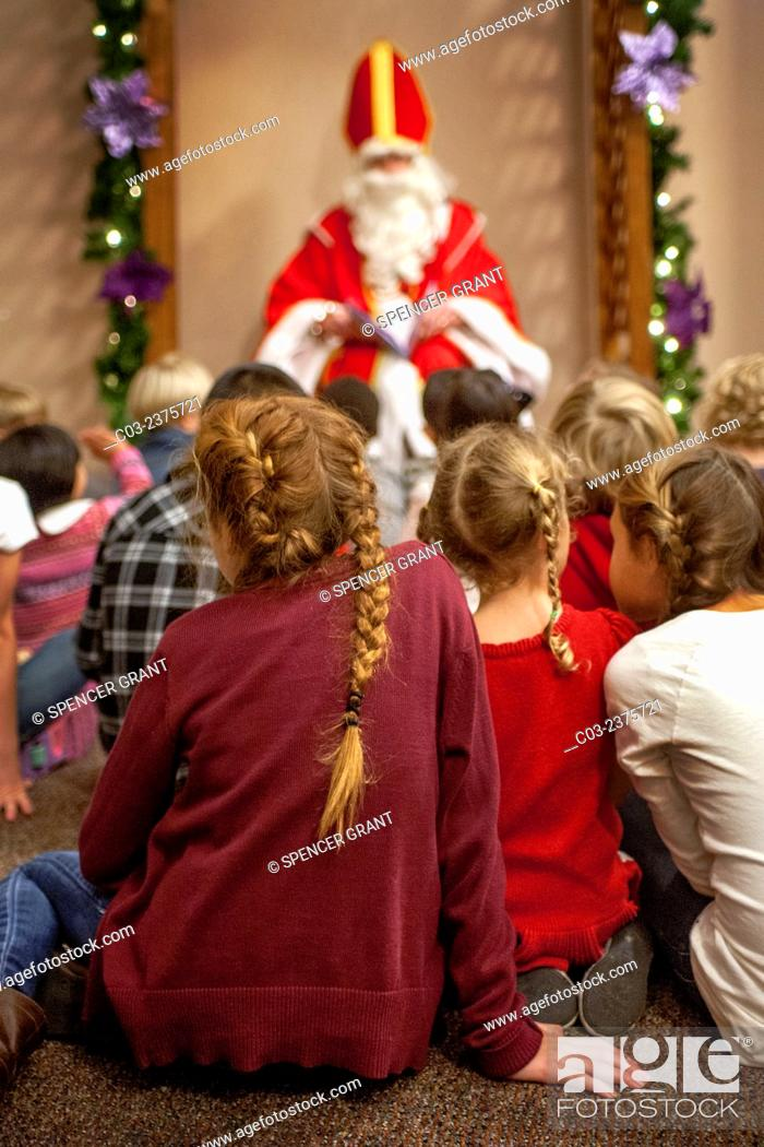 Stock Photo: Dressed as St. Nicholas, a volunteer at St. Timothy's Catholic Church, Laguna Niguel, CA, reads Christmas stories to multiracial parishioner children during.