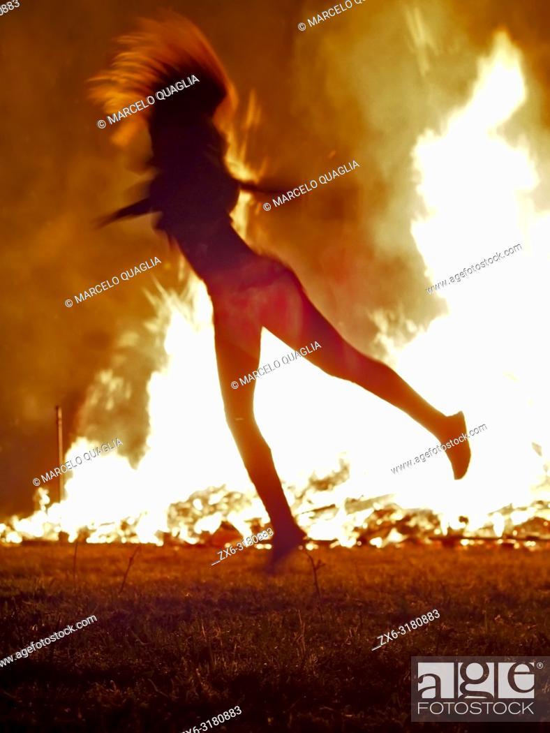 Stock Photo: Teenager girl dancing in front of Bonfire of St. John's Night –nit de Sant Joan- celebrating Summer Solstice arrival. Olost village.