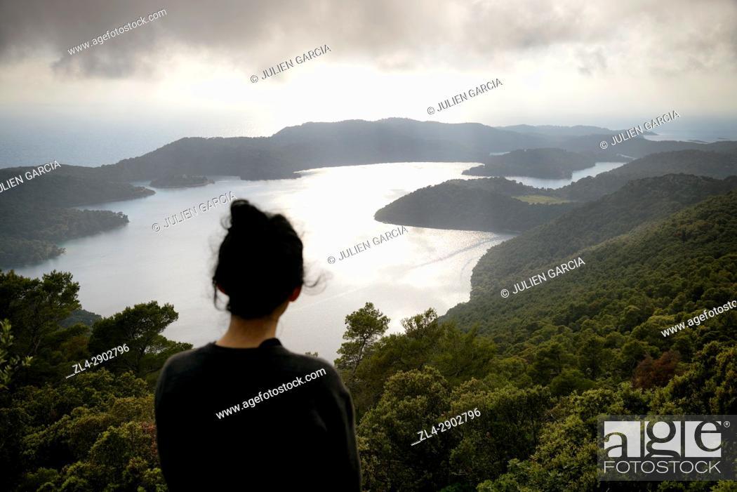 Stock Photo: Croatia, Dalmatia, Dalmatian Coast, Mljet island, Mljet National Park, woman watching the view on Veliko Jezero (large lake) from the summit of Montokuc peak.